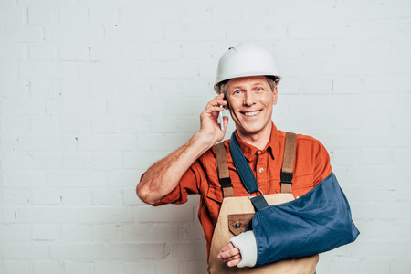 repairman with arm bandage talking on smartphone at white textured background