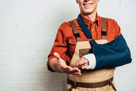 vista ritagliata del riparatore con fasciatura del braccio in piedi su sfondo bianco strutturato Archivio Fotografico