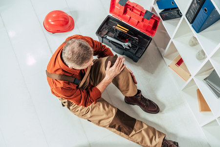 top view of repairman sitting on floor and holding injured knee surrounding by equipment in office Archivio Fotografico - 117863527