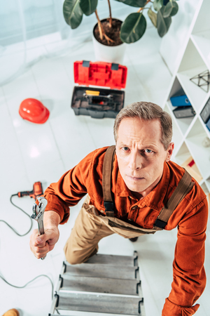 top view of climbing repairman on ladder with wrench in uniform in office Stock Photo