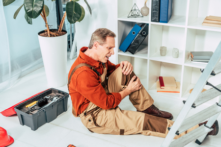 repairman sitting on floor and holding injured knee surrounding by equipment in office Reklamní fotografie