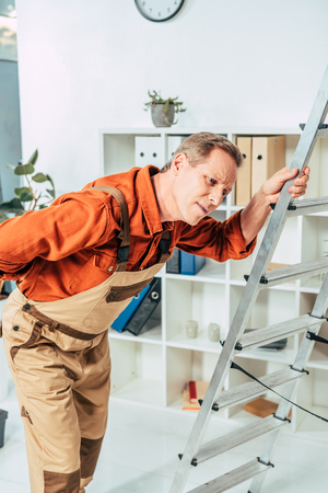 repairman standing and holding on ladder and back in office