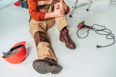 cropped view of repairman sitting on floor and holding injured knee in office Archivio Fotografico - 117863539