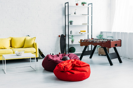furnished spacious living room with beanbag chairs, sofa and football table