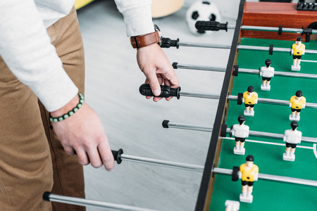 cropped view of man in white sweatshirt and brown jeans playing table football