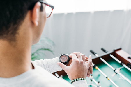 cropped view of man checking time on wristwatch while standing by football table