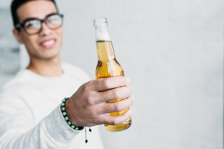 smiling mixed race man in glasses holding bottle of beer in stretched hand