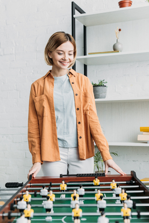 smiling pretty girl in orange shirt and white jeans standing by football table Stock Photo