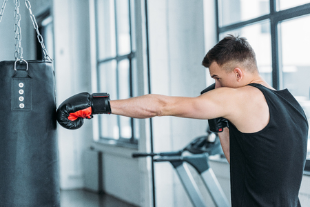 side view of muscular young man boxing with punching bag in gym