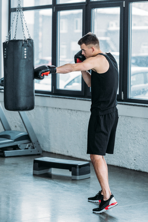 side view of young sporty man boxing with punching bag in gym