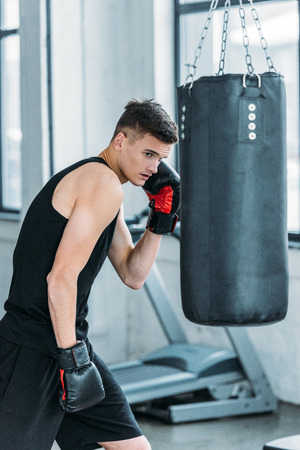 athletic young man in boxing gloves training with punching bag in gym