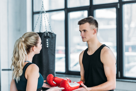 young male trainer giving boxing gloves to sporty young woman in gym