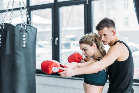 male trainer and sporty girl in boxing gloves exercising with punching bag in gym