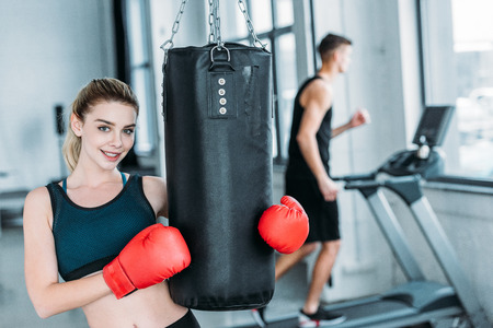 attractive sporty girl in boxing gloves holding punching bag and smiling at camera in gym