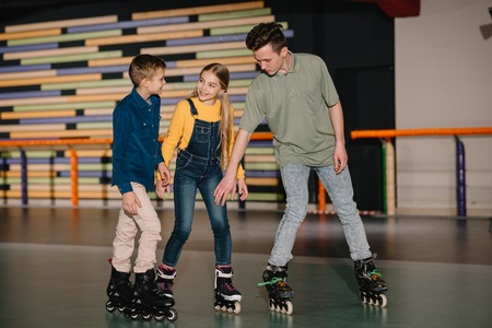 Young trainer explaining skating technics to attentive children