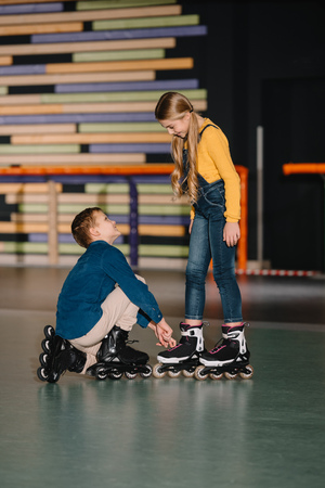 Selective focus of careful boy helping smiling friend with fixing roller skate boot