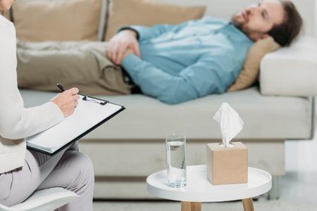 수염 난 남자가 소파에 누워 있는 동안 클립보드에 쓰는 심리 치료사의 자른 샷 스톡 콘텐츠