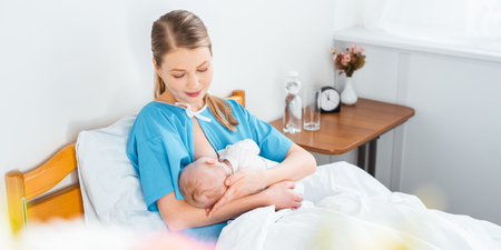 high angle view of smiling young mother breastfeeding newborn baby in hospital room
