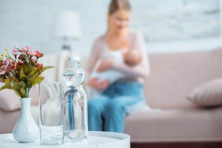 Vista cercana de vidrio, botella de agua, flores en florero y madre amamantando al bebé detrás en casa