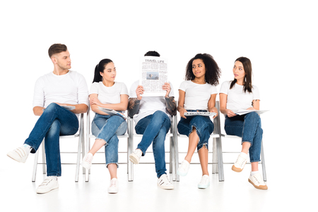 multiethnic group of young people sitting on chairs with crossed legs and looking at man with newspaper and obscure face isolated on white