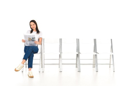 attractive girl sitting on chair with crossed legs and reading newspaper isolated on white Stock Photo