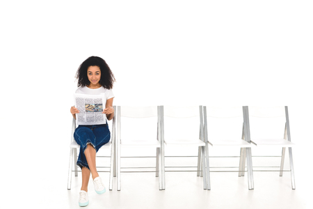 african american girl sitting on chair with crossed legs and newspaper while looking at camera isolated on white