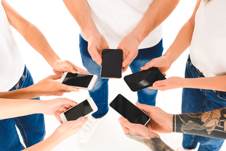 cropped view of group of people standing in circle and holding smartphones with blank screens in hands isolated on white