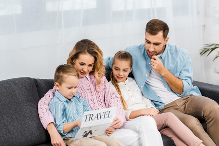 family sitting on sofa and reading travel newspaper in living room