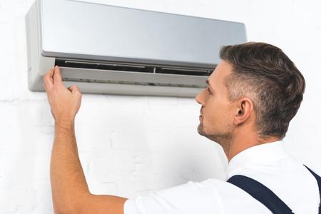 handsome repairman fixing air conditioner Reklamní fotografie