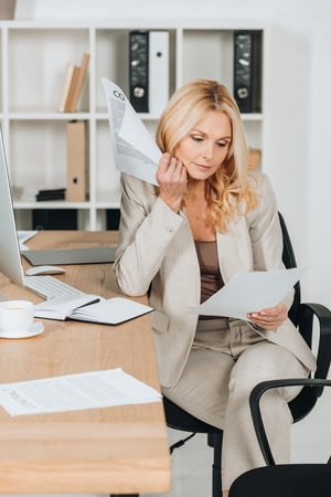 serious mature businesswoman working with papers while sitting at workplace