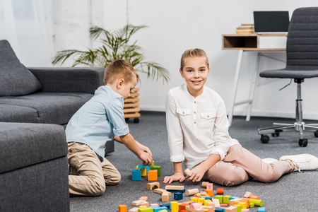 cute girl sitting on floor and looking at camera while boy  playing with multicolored wooden blocks in apartment 写真素材