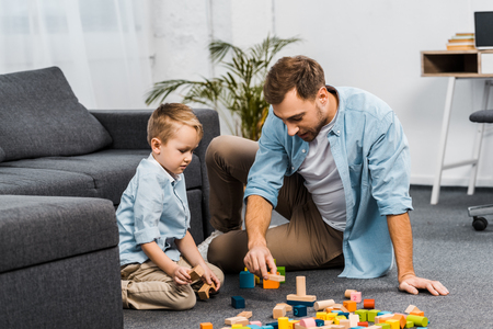 handsome man and cute boy playing with multicolored wooden blocks on floor in apartment