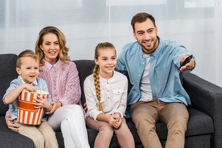 handsome father sitting on sofa and changing channels by remote controller with smiling  wife and daughter and son eating popcorn in apartment