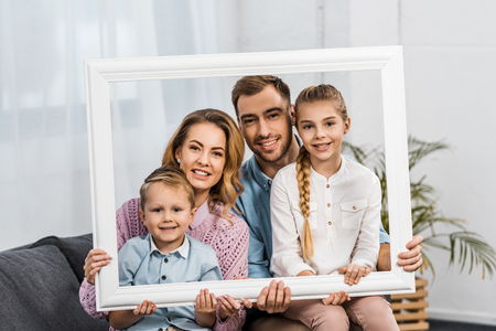 happy family holding white frame and looking at camera in living room