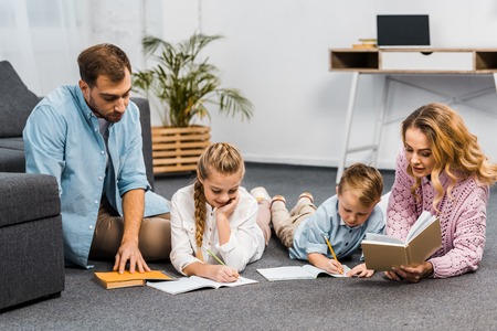 parents reading books while siblings writing in exercise books on floor in apartment