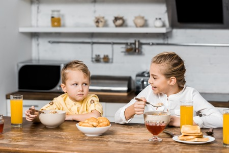 smiling girl holding spoon with porridge and looking at upset little brother at table