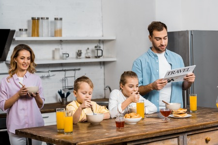 son and daughter eating oatmeal while father reading travel newspaper in kitchen