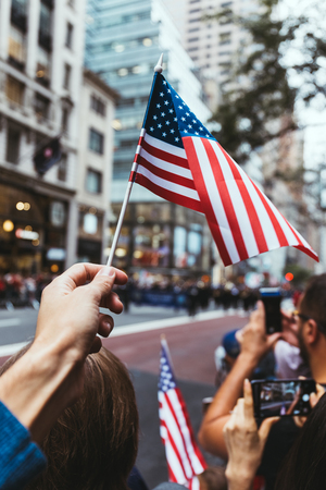 partial view of man holding american flag during parade on street in new york, usa 스톡 콘텐츠