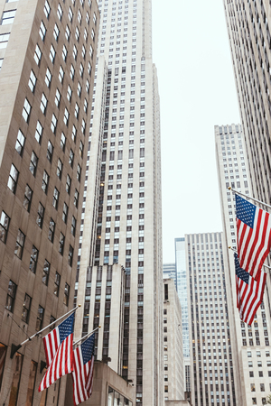 low angle view of skyscrapers and american flags on new york city street, usa
