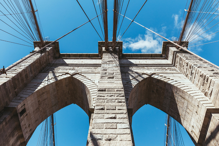 bottom view of brooklyn bridge against blue cloudy sky background in new york, usa