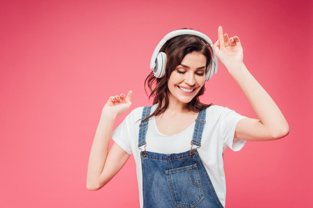 woman listening music in headphones isolated on pink