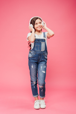full length of cheerful kid listening music and touching headphones on pink background Stock Photo - 117772044