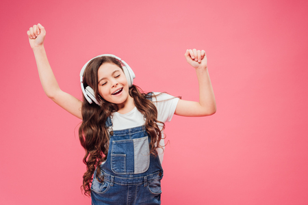 child with closed eyes and headphones dancing isolated on pink