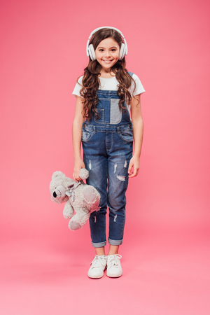 full length of smiling child standing in headphones and holding teddy bear on pink background Stock Photo