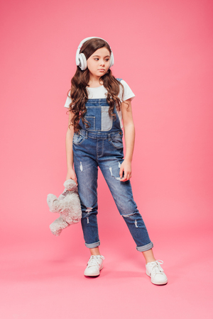 full length of sad kid standing in headphones and holding teddy bear on pink background Stock Photo