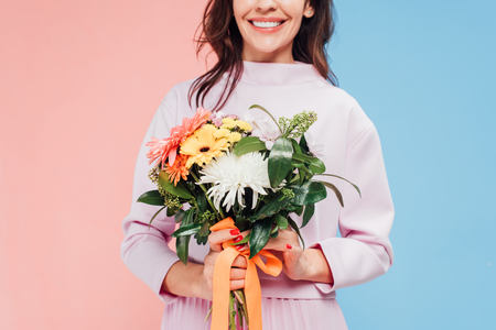 cropped view of smiling woman holding flowers in hands on happy mothers day