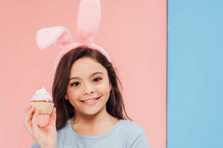 adorable child in bunny ears holding cupcake and looking at camera on blue and pink background Stock Photo