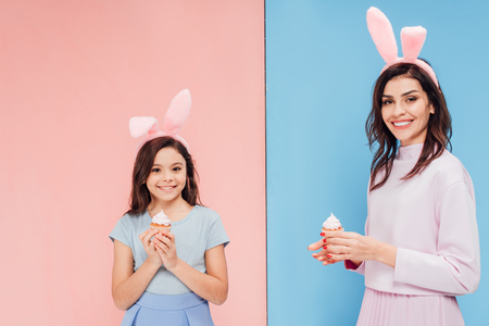 beautiful woman and child in bunny ears holding cupcakes and looking at camera on blue and pink background