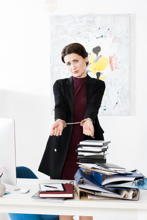 sad businesswoman showing hands with handcuffs in office