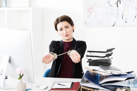 sad businesswoman showing hands with handcuffs at table in office